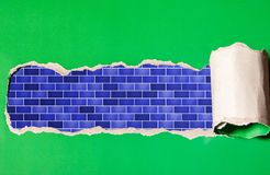 Torn strip of green paper with blue brickwork stock image