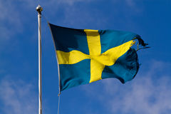 Torn swedish flag. Against deep blue sky Royalty Free Stock Images