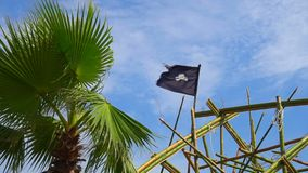 Torn tattered pirate flag waves in the wind tied to rigging on tall ship Dewarcuci as clouds pass with blue sky.  stock footage