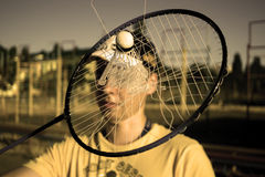 Torn tennis badminton racket with stuck shuttlecock inside during play match Royalty Free Stock Photo