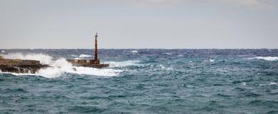 Torn, vågbrytare och fyr att motstå det rå havet och höga vågor arkivfoton