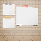 Torn white blank paper sheets stuck on brown brick wall Stock Photos