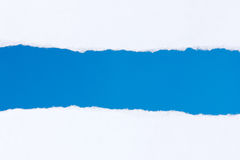 Torn white paper with a blue background royalty free stock image