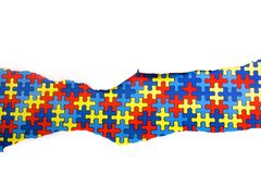 Torn white paper on multicolored puzzle background. Cocept for autism awareness day. Break barriers together for autism. Top view royalty free stock photography