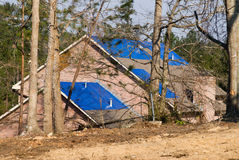 Tornado damaged house with a blue tarpaulin on the roof Royalty Free Stock Images