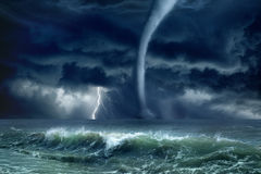Tornado, lightning, sea. Nature force background - huge tornado, bright lightning in dark stormy sky, stormy sea, big waves stock photo