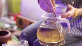 Tornado magnífico hecho de té en la tetera de cristal Té cereomy metrajes