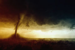 Tornado. Nature force background - dark stormy sky, huge tornado hits small town Stock Photos
