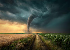 Tornado pegado en campos agrícolas en la puesta del sol fotografía de archivo