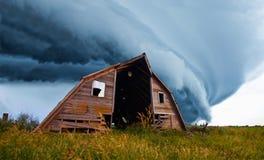 Tornado que forma detrás de granero viejo Imágenes de archivo libres de regalías