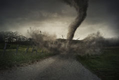 Tornado on road. A tornado spins down on a gravel road and destroys a fence