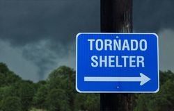 Tornado Shelter Sign With A Small Funnel Cloud On Background Royalty Free Stock Photos
