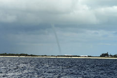 Tornado storm. Tornado touching down on land viewed from a body of water Stock Photos