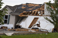 Tornado Storm Damage House Home Destroyed by Wind. Tornado wind and storm wreaks severe damage onto a residential family home. The structure is damaged beyond Royalty Free Stock Images