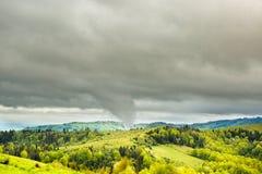 Tornado tip touching mountain. Royalty Free Stock Photo