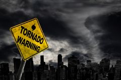 Tornado Warning Sign Against City Silhouette With Copy Space. Tornado warning sign against a powerful stormy background with city silhouette and copy space royalty free stock photo