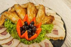 Torne côncavo das asas e da carne de galinha dos tartlets cortadas com a presença de folhas da alface foto de stock