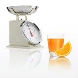 Torne mais pesada a escala com o vidro do suco de laranja isolado no backgroun branco Imagens de Stock Royalty Free