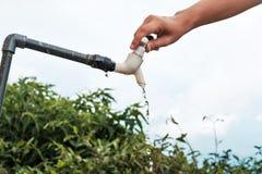 Torneira de água de fechamento da mão caucasiano da mulher no jardim Imagens de Stock