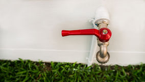 Torneira de água vermelha no jardim Imagens de Stock Royalty Free