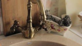 Torneira de cobre velho da cozinha com gotejamentos da água corrente vídeos de arquivo