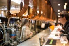 Torneira do bar da barra da cerveja, contador com fundo do bar do borrão Bruxelas Bélgica Foto de Stock Royalty Free