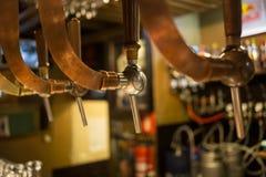 Torneira do bar da barra da cerveja, contador com fundo do bar do borrão Bruxelas Bélgica imagem de stock