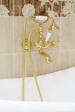 Torneira dourado com cabeças de chuveiro no banheiro vazio. Foto de Stock