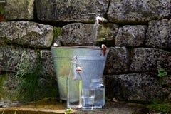 Torneira exterior com cubeta, garrafa e vidros Imagens de Stock Royalty Free