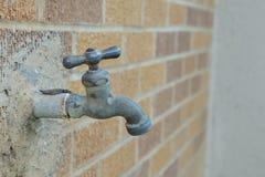 Torneira unido à parede de tijolo Fotografia de Stock