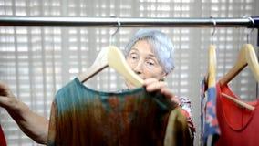 Torneiras da vendedora uma mulher idosa no ombro perto da cremalheira da roupa filme