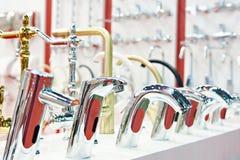 Torneiras de água na loja imagem de stock