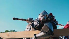torneo di #2 Gli uomini forti in armatura d'acciaio con le armi a disposizione stanno combattendo vicino ad un recinto di legno c video d archivio