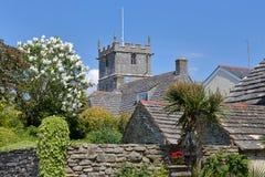 Tornet av kyrkan för St Edward ` s med stenhälltak och det lila trädet i förgrunden i Corfe rockerar arkivbild