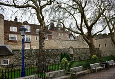 Tornet av London med blått och en guld- streetlight, träd och träbänkar byggnadskungarikelondon gammalt torn eniga victoria arkivfoto