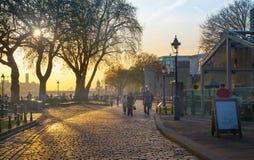 Tornet parkerar i soluppsättning FlodThemsensidan går med folk som vilar vid vattnet London Arkivbild