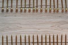 Tornillos amarillos en dos filas en fondo de madera Foto de archivo