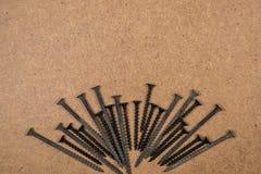 Tornillos de madera en el panel de fibras de madera Fotos de archivo