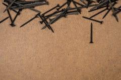 Tornillos de madera en el panel de fibras de madera marrón Imagen de archivo