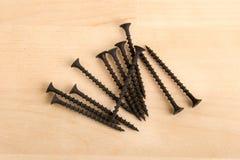 Tornillos de madera negros en fondo de madera fotos de archivo