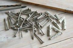 Tornillos de madera y anclas plásticas en tablones de madera Imagen de archivo libre de regalías