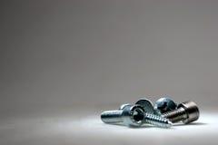 Tornillos en un fondo gris Imagen de archivo libre de regalías