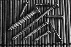 Tornillos monocromáticos aislados en la textura de madera para los dispositivos móviles del ot del sitio web, muestra nacional de fotos de archivo