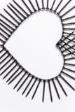 Tornillos negros presentados en la forma de un corazón en un fondo blanco fotografía de archivo