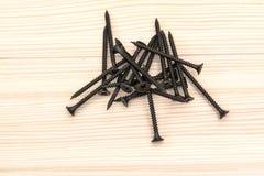 Tornillos negros que mienten en una superficie de madera imagen de archivo libre de regalías