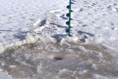 Tornillos y agujeros del hielo en el hielo Imagen de archivo libre de regalías
