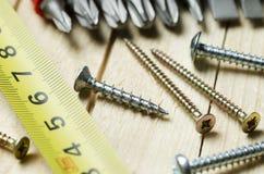 Tornillos y cinta métrica en los tableros de madera foto de archivo