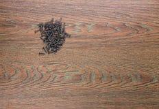 Tornillos y destornillador metálicos negros en un fondo de madera Imágenes de archivo libres de regalías
