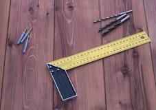 Tornillos y regla en una tabla de madera Fondo de madera Foto de archivo