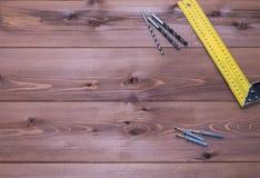 Tornillos y regla en una tabla de madera Fondo de madera Foto de archivo libre de regalías